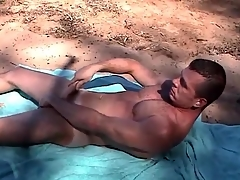 Muscular gay guy jerks off on a public beach