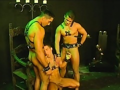Three slaves in their leather harnesses are unengaged around have a trio