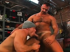 Muscled gay mechanics engage nigh a hardcore threesome nigh the garage